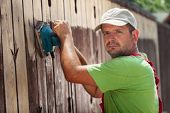 Man removing old cracked paint from a fence royalty free stock image