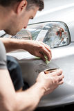 Man removing scratches from car bumper Royalty Free Stock Images