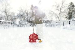Man removing snow on the backyard with the shovel during snowfall Royalty Free Stock Photo