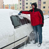Man removing snow from car. A man removing snow from his car in winter stock image