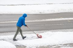 Man Removing Snow in His Driveway with a Shovel 4. A young man removing snow from his driveway with a shovel 4 royalty free stock photos