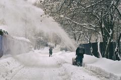 Man removing snow from the moscow street using snow blower. After big snowfall stock image