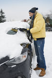 Man removing snow off the car Stock Image