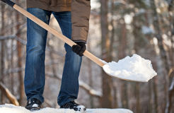 Man removing snow from a roof. With a shovel stock photography