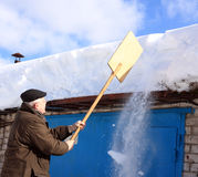 Man removing snow from a roof with a shovel Stock Image