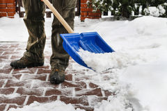 Man removing snow from the sidewalk after snowstorm Stock Image