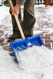 Man removing snow from the sidewalk after snowstorm Stock Photo