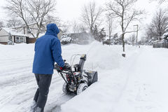 Man Removing Snow with a Snow Blower #3. Man clearing snow with a gas snow blower in a suburb #3 royalty free stock photos