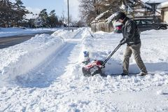 Man Removing Snow with a Snowblower on a Sunny Day  3. Back View of a Man Removing Snow with a Snowblower on a Sunny Day  3 Stock Photos