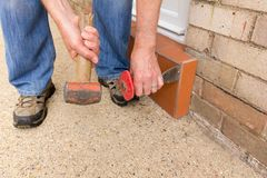 Man using a hammer and bolster. Man removing tiles from a doorstep with a hammer and bolster royalty free stock photos