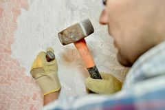 Man removing tiles from wall with hammer and chisel. Tiles royalty free stock image