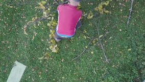 Man removing tree branches. A man removing tree branches from the ground, above view stock video