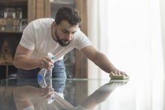 Man rengöringar fönstren av huset med pulverizeren den som kan användas till mycket för det glass rengöringsmedlet Arkivbilder