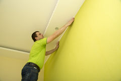 Man renovates room interior with a plastic molding Stock Image
