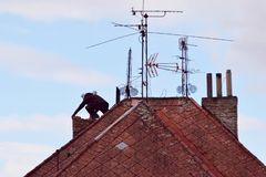 Man renovating an old chimney on the rooftop stock photos