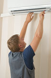Man repair air-conditioner Stock Photo