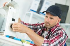 Man repairer working in workshop and repairing device Stock Photos
