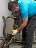 Man repairing air conditioner. Hispanic man fixing a central air conditioning unit outside Royalty Free Stock Image