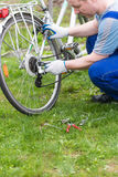 Man repairing a bicycle stock images