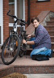 Man repairing bicycle on porch of his house. Young men repairing bicycle on porch of his house Royalty Free Stock Photos