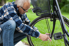 Man repairing bicycle wheel. Horizontal view of a man repairing bicycle wheel outdoors Royalty Free Stock Photos