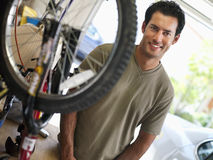 Man repairing bicycle on workbench in domestic garage, smiling, side view, portrait Royalty Free Stock Photography