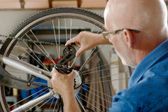 Man repairing bike gear in his workshop. Royalty Free Stock Photo