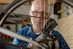 Man repairing bike gear in his workshop. Stock Images