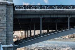 A man is repairing a bridge across the river. A man is repairing a bridge across the Moscow river near church, winter Stock Photo