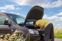 Man repairing a broken car by the road Stock Photography