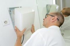 Man repairing broken dryer. Man repairing a broken dryer Stock Photography