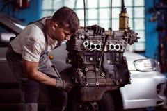 Man repairing broken engine. Photo of man in uniform repairing broken engine Royalty Free Stock Photos