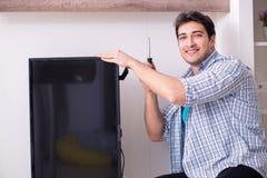 The man repairing broken tv at home. Man repairing broken tv at home Stock Photo