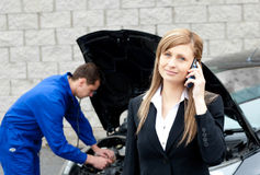 Man repairing car of a businesswoman Royalty Free Stock Image