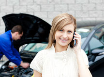 Man repairing car of phoning woman Royalty Free Stock Images