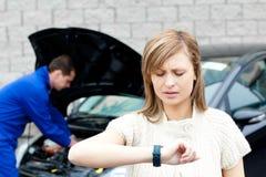 Man repairing car of pretty woman Stock Photography