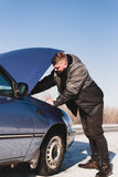 Man repairing a car standing at the hood. Man stands near his broken car in winter Royalty Free Stock Images