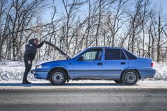 Man repairing a car standing at the hood. Man stands near his broken car in winter Royalty Free Stock Photo