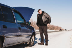 Man repairing a car standing at the hood. Man stands near his broken car in winter Royalty Free Stock Photos