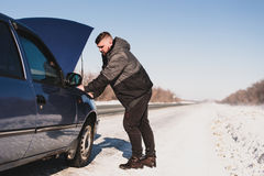Man repairing a car standing at the hood. Man stands near his broken car in winter Stock Photography