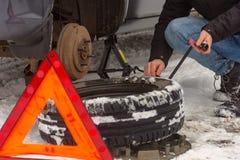 Man repairing a car wheel on a snow road. Ð•mergency sign royalty free stock photo