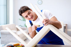 The man repairing chair in the room Stock Image