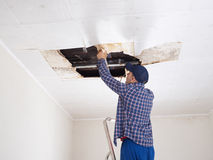 Man repairing collapsed ceiling. Royalty Free Stock Photography