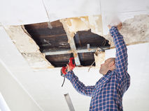 Man repairing collapsed ceiling Royalty Free Stock Photos