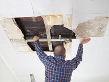 Man repairing collapsed ceiling. Royalty Free Stock Images
