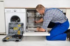 Man Repairing Dishwasher Royalty Free Stock Photography