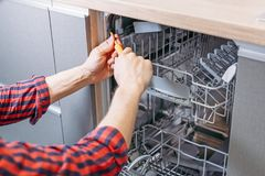 Man repairing dishwasher. Male hand with screwdriver installs kitchen appliances. Close up royalty free stock photo
