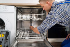 Man Repairing Dishwasher Stock Photo