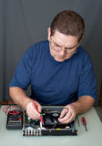 The man repairing DVD a player. The man with a screw-driver and a tweezers repairing DVD a player royalty free stock photography