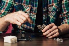 Man repairing e-evaporator. Maintenance of electronic mech mod vaping device.Modern vaporizer e-cig gadget to vape glycerin e-liquid.Vaper device repair service royalty free stock images